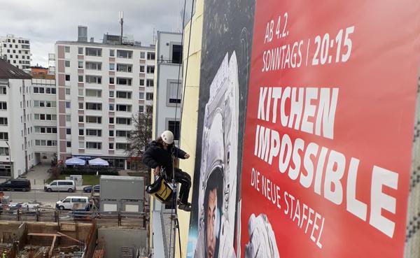 Ein Teclimb Höhenarbeiter bei der Installation eines Werbeplakats für den Sender VOX